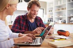 坐在他们的厨房里的夫妇使用膝上型计算机 免版税库存照片