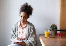在家坐写在笔记本的微笑的少妇 免版税库存图片