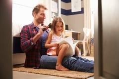 掠过年轻女儿的头发的父亲 免版税库存照片