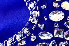 关闭与衣服饰物之小金属片和假钻石的蓝色织品 免版税库存图片