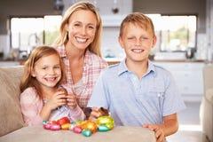 在家庆祝复活节与孩子的母亲 免版税图库摄影