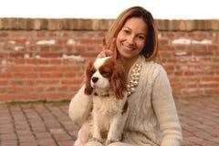美丽的女孩做室内天线对她的狗骑士国王查尔斯狗在红砖台阶 免版税库存图片