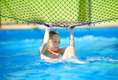 Милый ребенк мальчика имея потеху, делая эффектное выступление на сети волейбола в бассейне Стоковые Изображения