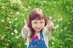 Το πορτρέτο του χαριτωμένου μικρού κοριτσιού με τους αντίχειρες παρουσιάζει μια κατηγορία στο λιβάδι λουλουδιών, ευτυχής έννοια π Στοκ Εικόνα