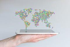 漂浮在一种现代巧妙的电话或片剂上的世界地图 拿着在灰色背景前面的手移动设备 免版税库存图片