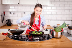 烹调在厨房里的年轻可爱的妇女 库存照片