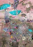 两个女孩在与发光的浅兰的伞的雨中走 免版税库存图片