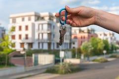 给房子钥匙的房地产开发商一个新的财产所有人 免版税库存照片