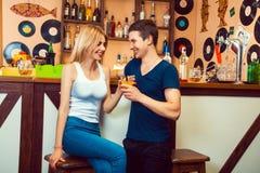 挥动与酒吧的一个金发碧眼的女人的人和给她一个鸡尾酒 免版税库存照片