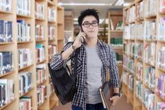 时髦学生谈话在电话在图书馆里 免版税库存图片