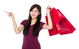有购物袋的亚洲妇女举行和手指向上指向 库存照片