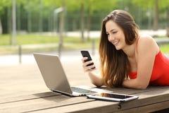 使用膝上型计算机和巧妙的电话的女孩在公园 免版税图库摄影