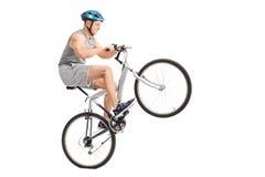 做有他的自行车的快乐的年轻骑自行车的人一个自行车前轮离地平衡特技 库存照片