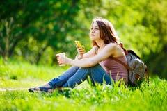 使用她的智能手机的妇女和食用咖啡 免版税库存图片