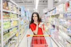 妇女丝毫在超级市场的购物单 免版税库存图片
