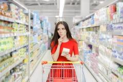 好奇妇女在有购物单的超级市场 免版税图库摄影