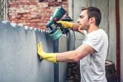 Человек используя защитные перчатки крася серую стену с краской для пульверизатора дает полный газ Молодой работник восстанавлива Стоковые Фотографии RF