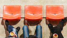 Строка пластичных стульев и ног в футбольном стадионе Стоковое фото RF