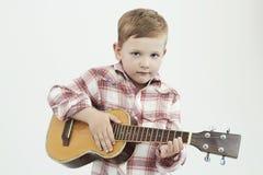 有吉他的滑稽的儿童男孩 演奏音乐的时兴的乡村男孩 免版税库存图片