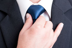 修理蓝色领带的成功的经理 免版税库存照片
