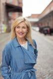 站立在街道微笑的愉快的白肤金发的妇女 免版税库存图片