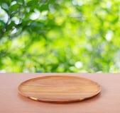 在桌上的空的圆的木盘子在迷离树背景 免版税库存图片