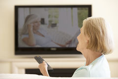 在家看宽银幕电视的资深妇女 免版税库存图片