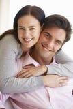 一起放松在沙发的年轻夫妇在家 免版税库存图片