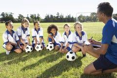 Группа в составе дети в футбольной команде имея тренировку с тренером Стоковые Фото