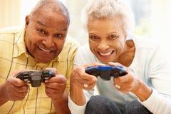 打计算机游戏的资深夫妇 图库摄影