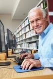 研究计算机的老人在图书馆里 免版税库存图片