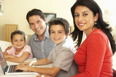 使用计算机的年轻西班牙家庭在家 免版税库存图片