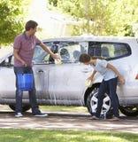 父亲和十几岁的女儿洗涤的汽车一起 免版税库存照片