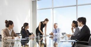 小组商人开委员会会议在玻璃表附近 免版税库存照片