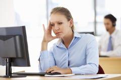 工作在书桌的被注重的女实业家在繁忙的办公室 免版税图库摄影