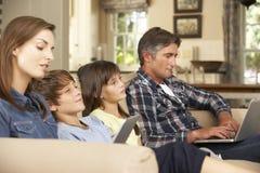 看电视的孩子,父母在家使用膝上型计算机和片剂计算机 免版税库存照片