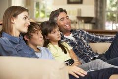 家庭在家坐一起看电视的沙发 免版税库存图片