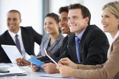 Группа в составе бизнесмены слушая к коллеге адресуя встречу офиса Стоковые Изображения RF
