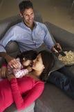 在沙发的西班牙家庭看电视和吃玉米花的 图库摄影