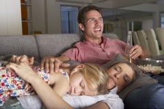 在沙发的家庭看电视和吃玉米花的 免版税库存照片