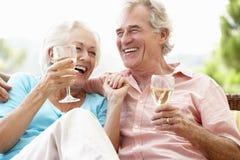 资深夫妇坐一起喝酒的室外位子 库存照片