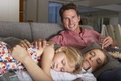 在沙发的家庭看电视和吃玉米花的 库存图片
