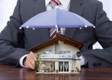 与伞和房子模型的商人 免版税库存图片