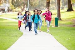 跑沿往照相机的道路的小组孩子在公园 免版税库存照片