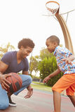 Πατέρας με την παίζοντας καλαθοσφαίριση γιων στο πάρκο από κοινού Στοκ Εικόνες