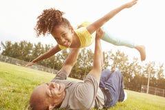 与孙女的祖父使用的比赛在公园 免版税库存照片