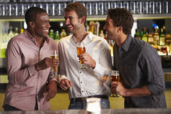 享受饮料的三个男性朋友在酒吧 免版税库存图片