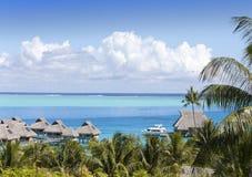 博拉博拉岛,波里尼西亚海岛的蓝色盐水湖  从高度的一个看法在棕榈树、传统小屋在水和海 图库摄影
