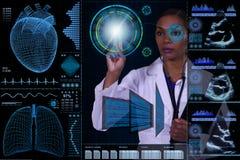 一位女性医生在漂浮在她前面的一台未来派计算机后是可看见的 免版税库存照片