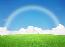 Πράσινος τομέας χλόης, μπλε ουρανός με τα σύννεφα στον ορίζοντα και ουράνιο τόξο Στοκ εικόνα με δικαίωμα ελεύθερης χρήσης